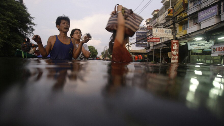 <p>Residents wade along a flooded street on the outskirts of Bangkok on Thursday. Clambering aboard bamboo rafts and army trucks, residents fled their homes as high waters moved closer to the heart of the city. </p>