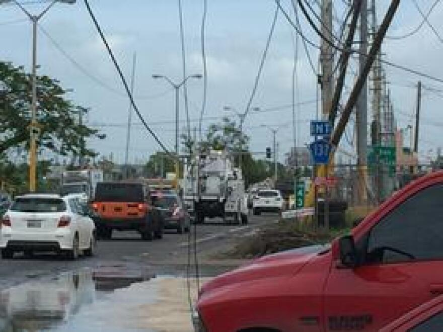 A street in Vega Baja with downed power lines hanging over traffic.