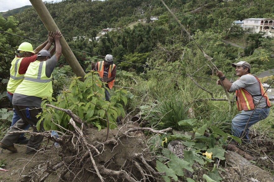 In this Jan. 31, 2018 photo, Public Works Sub-Director Ramon Mendez, wearing a hard hat at left, works with locals who are municipal workers, from right, Eliezer Nazario, Tomas Martinez and Angel Diaz as they install a new post to return electricity to Felipe Rodriguez's home, four months after Hurricane Maria hit the El Ortiz sector of Coamo, Puerto Rico. Coamo's city government relies on residents to tell it where damaged cables and posts are located, and uses hand-drawn maps to show homes that have power or need it, and the city updates the power company. (AP Photo/Carlos Giusti)