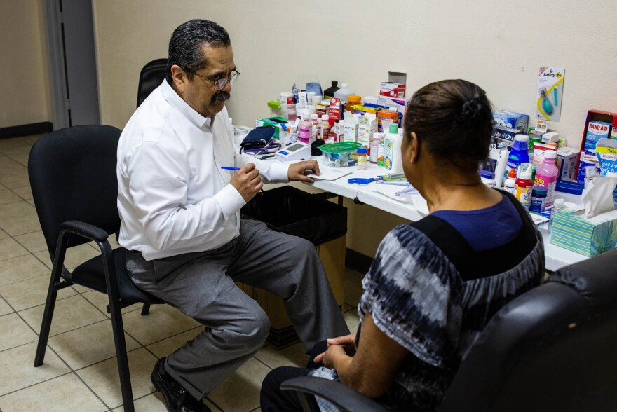At an ad hoc clinic in an old warehouse in El Paso, Dr. José Manuel de la Rosa discusses an insulin prescription with a woman who has diabetes.