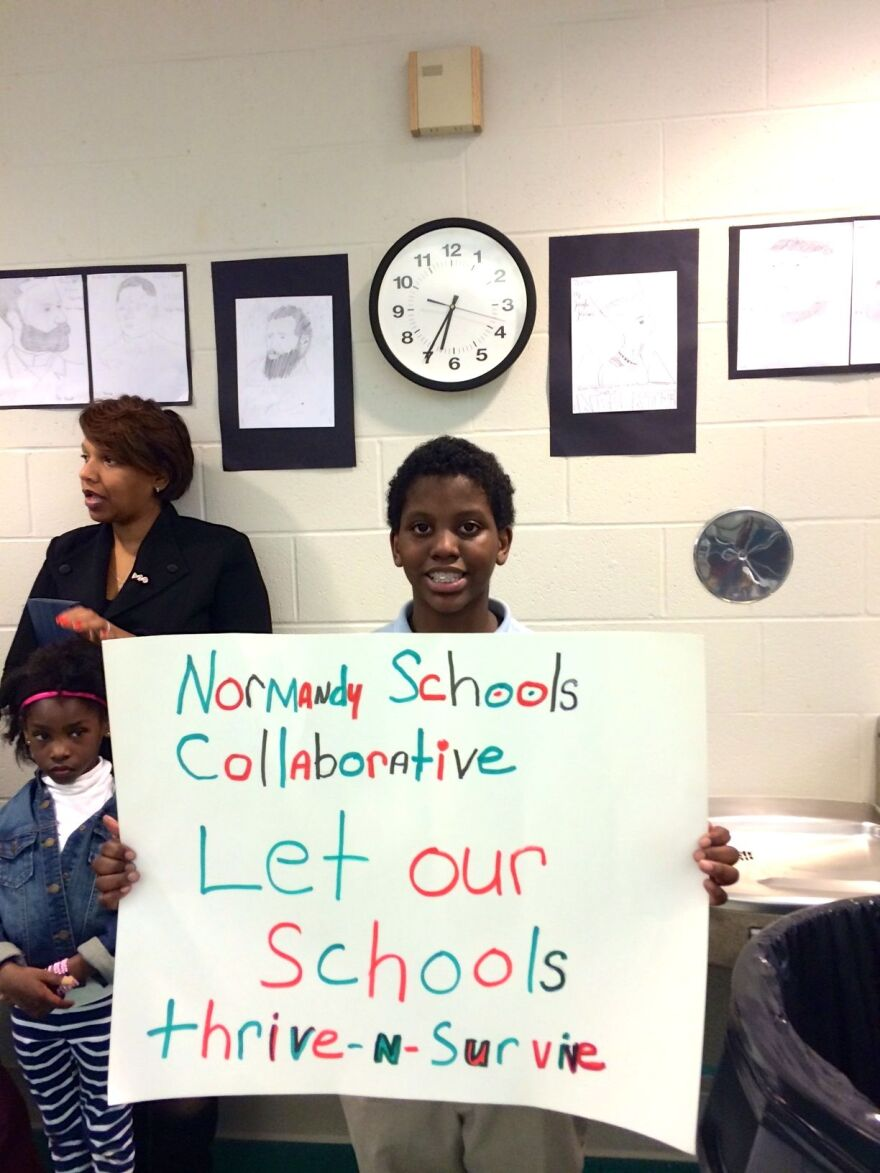 Normandy Middle School student Raheem Larry holds up a sign during Thursday night's board meeting