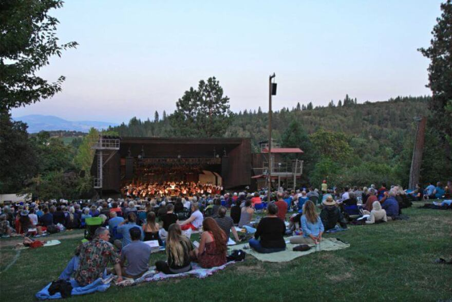 Image of crowd of people watching outdoor classical performance