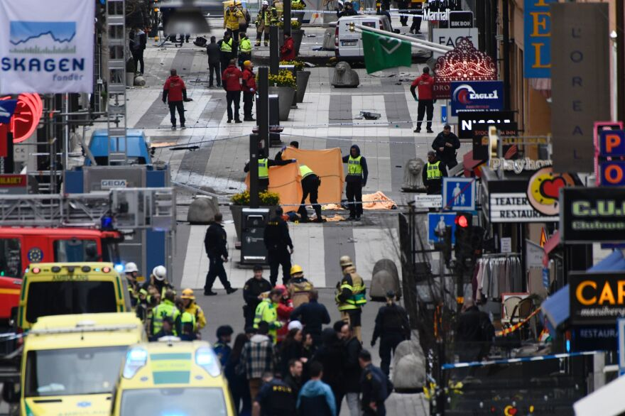 Emergency crews work at the scene where a truck crashed into the Ahlens department store in central Stockholm on Friday.