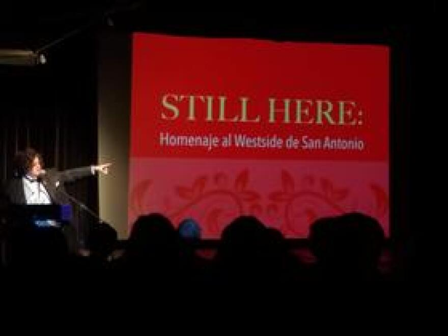 """Lourdes Pérez, musician, composer, poet, and creator of """"Still Here: Homenaje al Westside de San Antonio"""" stands before a crowd to present her work at the Esperanza Peace and Justice Center."""