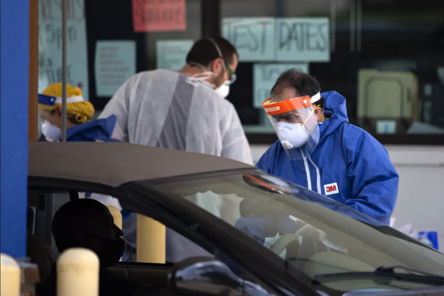 A person in a face shield and face mask and protective gear administers a test to a person in a car.