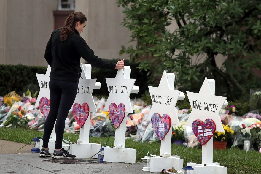 A visitor walks by a memorial outside the Tree of Life synagogue following Saturday's shooting in Pittsburgh on Monday.