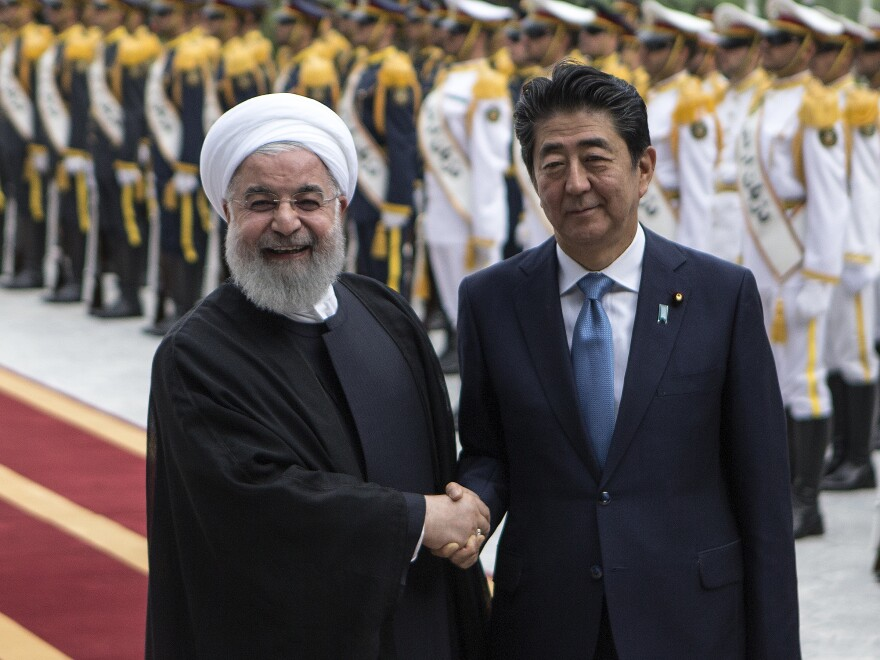 Japanese Prime Minister Shinzo Abe shakes hands with Iranian President Hassan Rouhani during a welcome ceremony in Tehran, Iran, on Wednesday. Abe is on a two-day official visit to Iran, where he hopes to mediate between Tehran and Washington.