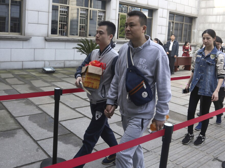 Sun Wenlin (left) and his partner, Hu Mingliang, hold hands as they arrive at the Furong District Court in Changsha to argue in China's first same-sex marriage case.