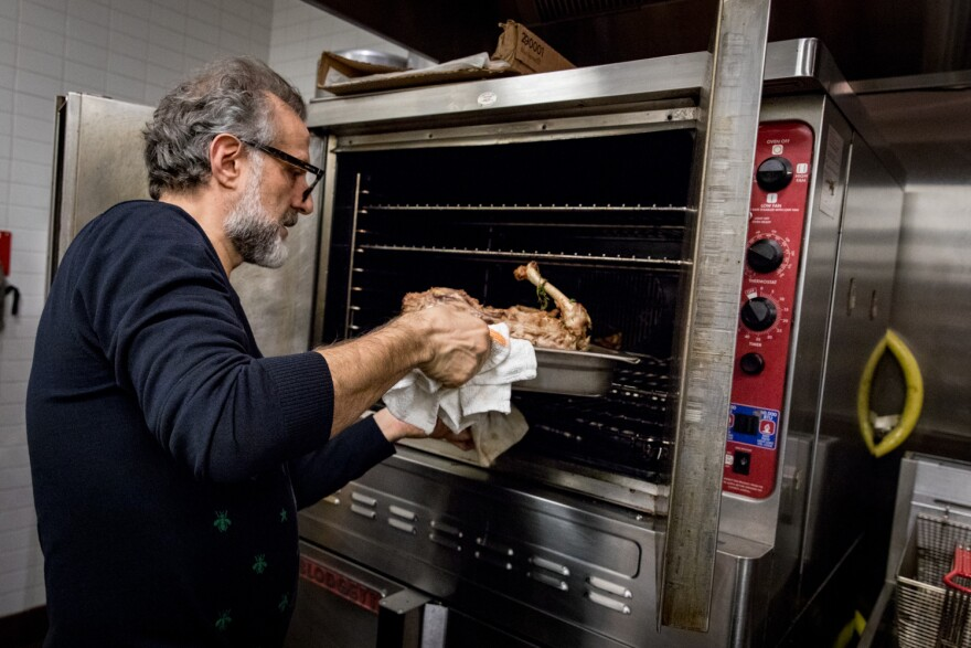 Bottura puts a turkey carcass, nestled on a baking sheet with veggie scraps, in the oven to roast and unlock its flavor. After about 45 minutes, the bones go in water to boil to become the broth for passatelli.