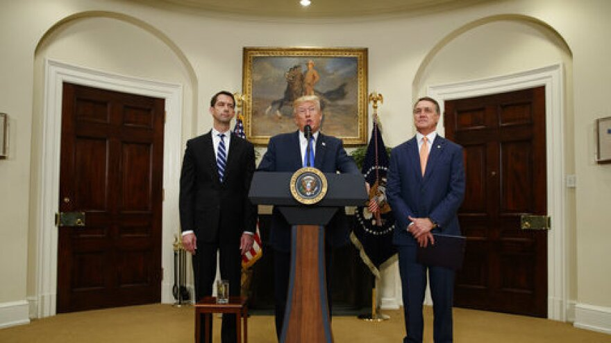 President Trump, flanked by Sens. Tom Cotton, R-Ark. (left), and David Perdue, R-Ga., speaks in the Roosevelt Room of the White House on Wednesday during the unveiling of legislation that would place new limits on legal immigration.