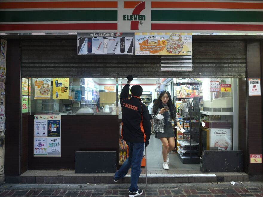 A last customer leaves as an employee pulls down the shutters at 5 p.m. at a convenience store normally open 24 hours a day in Hong Kong on Saturday.