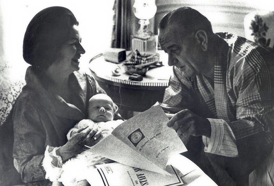 President Lyndon Johnson reads the President's Daily Briefing as his wife Lady Bird Johnson holds their first grandchild in the White House.