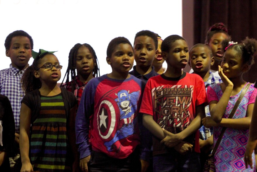 Students from Koch Elementary School sing for their fallen classmate Jamyla Bolden during Wednesday's Ferguson Commission meeting.