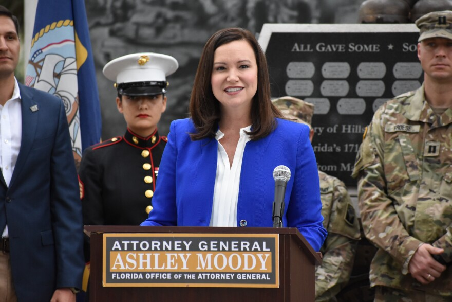 Woman speaks at podium with military members behind her