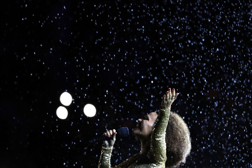 Singer Mariene de Castro performs in front of the Olympic flame before it was extinguished.