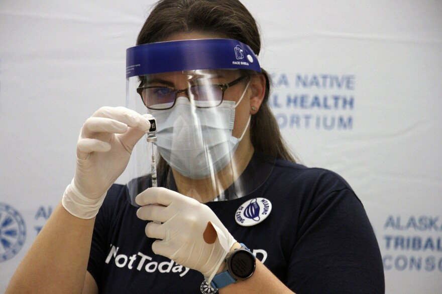 A pharmacist, wearing gloves and a mask, holds a COVID-19 vaccine shot.