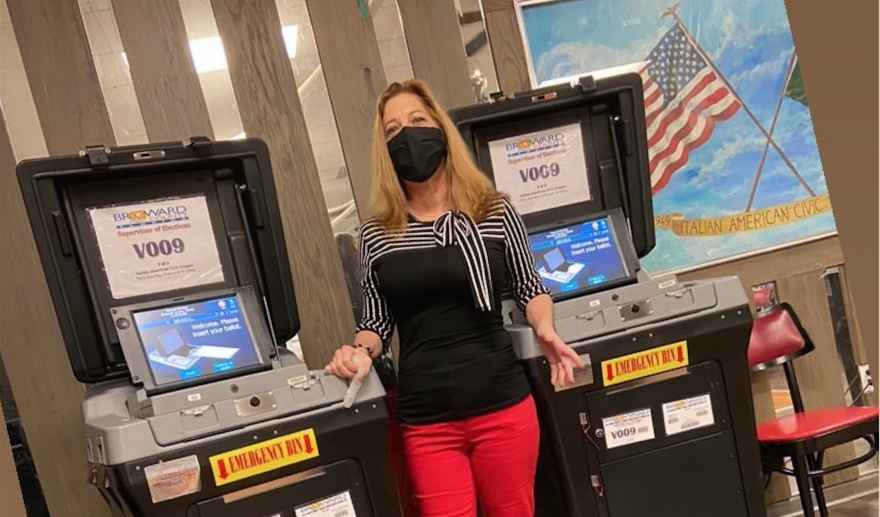 Woman in mask in front of poll machines.