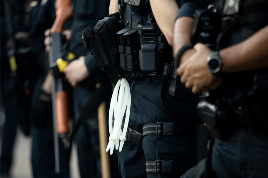 Austin police officers stand near an overpass on I-35 to prevent protesters from blocking traffic during a demonstration outside police headquarters.