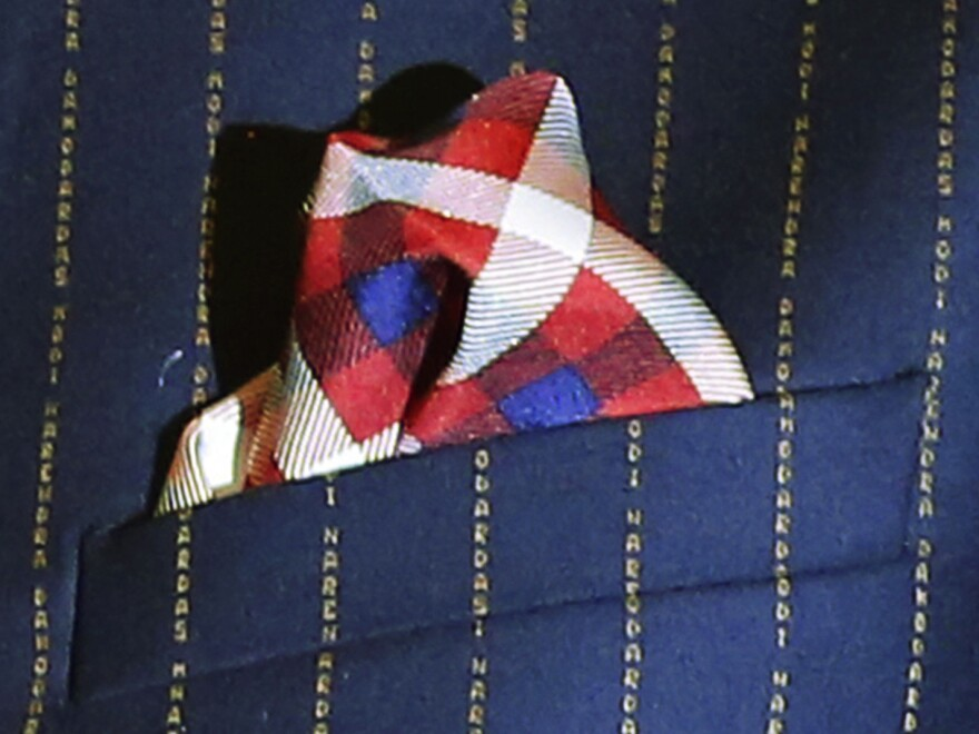 """A close-up view of Indian Prime Minister Narenda Modi's dark pinstripe suit, repeatedly embroidered with the words """"Narendra Damodardas Modi."""""""