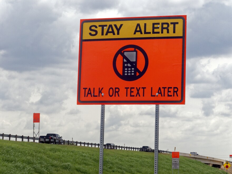 "Photo of a road sign that reads ""stay alert talk or text later"""