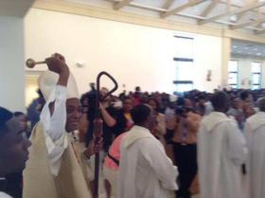 Cardinal Chibly Langlois blesses parishioner with holy water as he enter Notre Dame D'Haiti Catholic Church in Little Haiti.