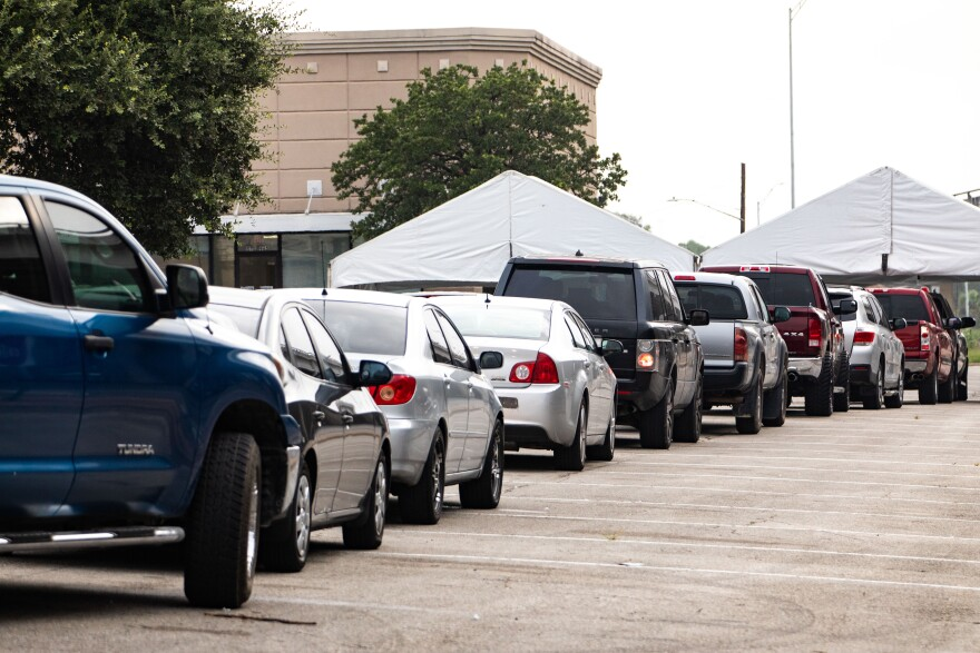 Cars line up at CommUnityCare's drive-thru testing site in Hancock Center on Thursday morning.