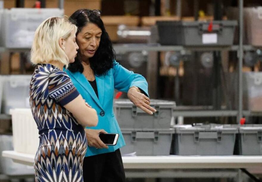 Palm Beach County Supervisor of Elections Susan Bucher checks her watch as she talks to an employee at the elections office during a machine recount on Thursday, Nov. 15, 2018, in West Palm Beach, Fla.