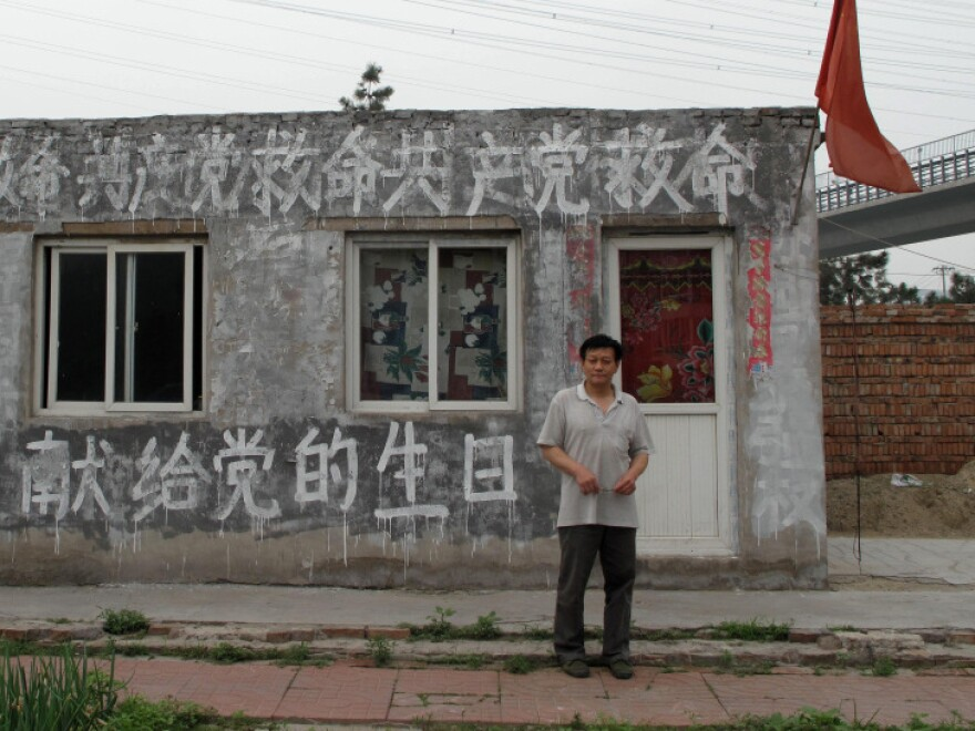 "Thirty-year Communist Party veteran Wang Jiang stands in front of his building, painted  with the words, ""Save me, CCP!"" He says his house was illegally demolished,  and he's now seeking justice rather than compensation. His aim is to shame the  Communist party into helping him."