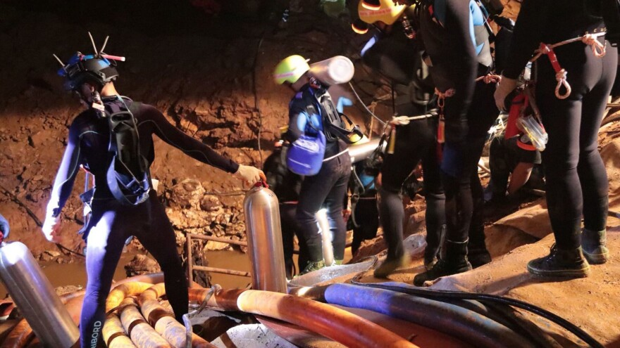 Thai rescue team members walk inside the cave where 12 boys and their soccer coach are trapped, in a photo released by Thai authorities on Saturday.