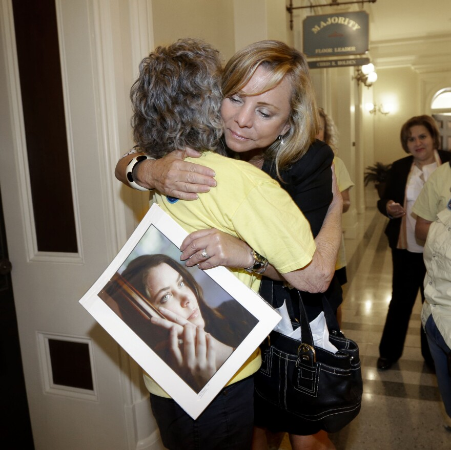 Debbie Ziegler holds a photo of her daughter, Brittany Maynard, as she receives congratulations from Ellen Pontac, after a right-to die measure was approved by the state Assembly, Wednesday, Sept. 9, 2015, in Sacramento, Calif.