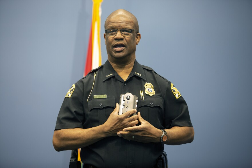 A uniformed officer holds up a smartphone-style camera and holster that will be equipped to the center of an officer's chest.