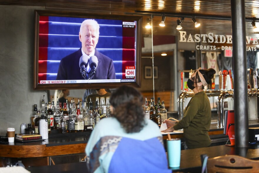Assistant manager Sarah Espinosa (right) and her friend, Taylor Malray, watch Joe Biden's inauguration as EastSide Tavern opens for the day.