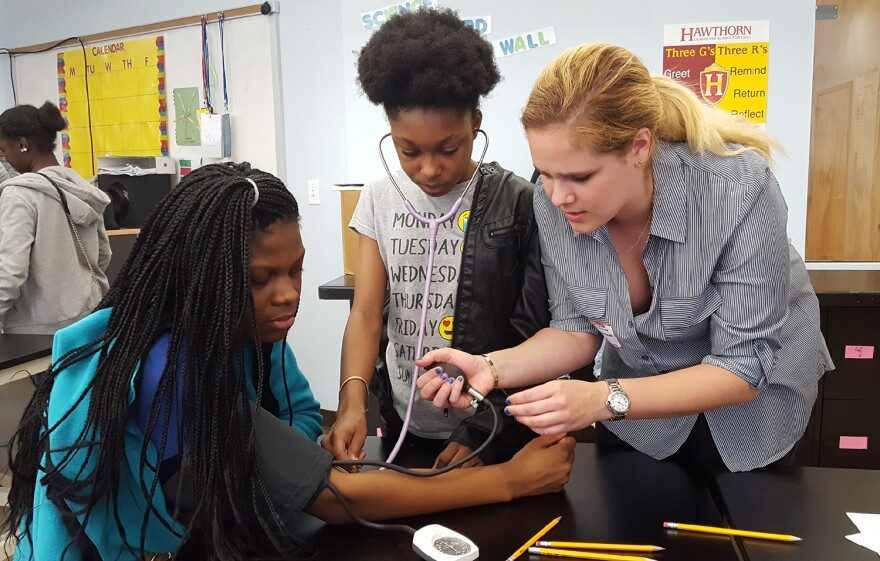 Hawthorn students Lanet Williams, at left, and Lauryn Holmes, center, practice taking each other's blood pressure with Washington University medical student Helen Liljenwall on April 13, 2018.