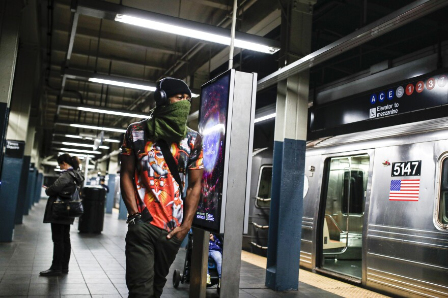 A subway customer walks a sparsely populated 42nd Street Times Square platform while covering his face due to coronavirus concerns in New York.