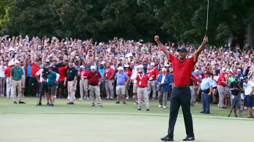 Tiger Woods celebrates making a par on the 18th green to win the Tour Championship at East Lake Golf Club Sunday in Atlanta.