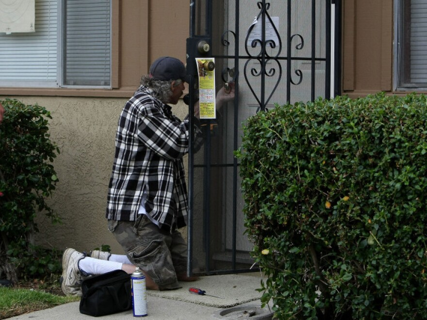 <strong>The Real Deal:</strong> Locksmiths are trying to find ways to warn the public against scam artists. In this file photo, a locksmith picks the lock of a foreclosed home in California.