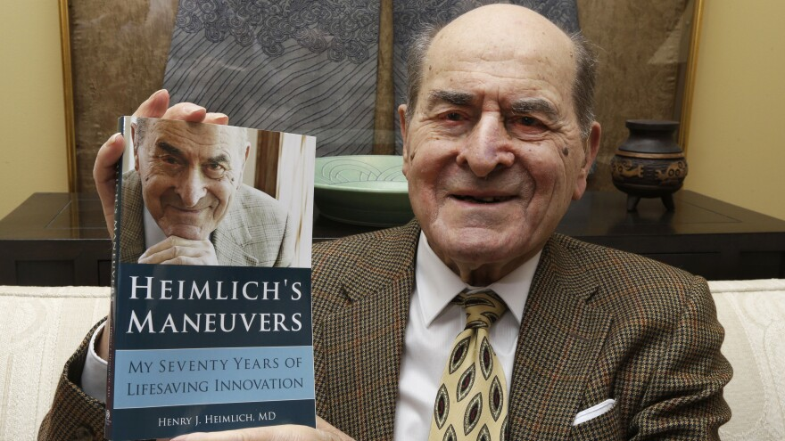 Dr. Henry Heimlich has died in Ohio at age 96. He's seen here in 2014, holding a copy of his memoir at his home in Cincinnati.