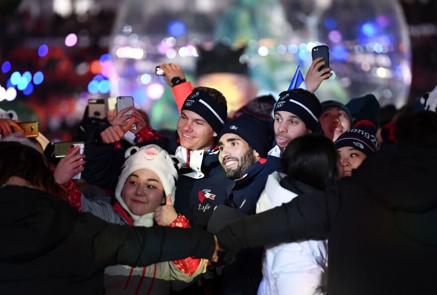 French biathlon champion Martin Fourcade (center), who won three gold medals in Pyeongchang, poses for a selfie with athletes and volunteers during the closing ceremony.