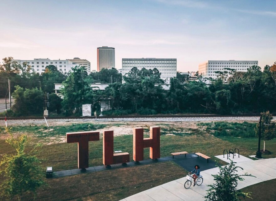 Woman on a Pace bike rides past the TLH sign in Cascades park.