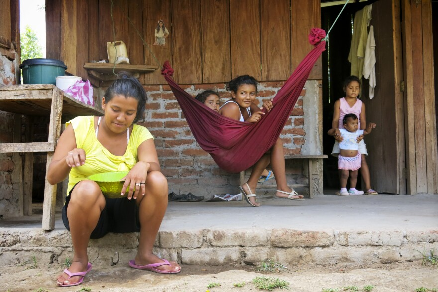 Ligda Bol, 19 years old, sits in front of her small farm. Her house, near the Brito River, is in the path of the proposed canal. Her family hasn't been told if she'll be forced to move, when a decision will be made or how she will be compensated for her farm.
