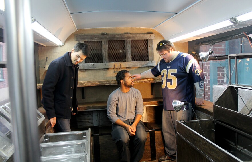 From left: Lucas Signorelli, Jeremy Goss and Colin Dowling chat as they move to sit on a bench on the back of the retrofitted bus on Dec. 6, 2015. Signorelli will take over as executive director of MetroMarket in 2016. Goss and Dowling cofounded the organ