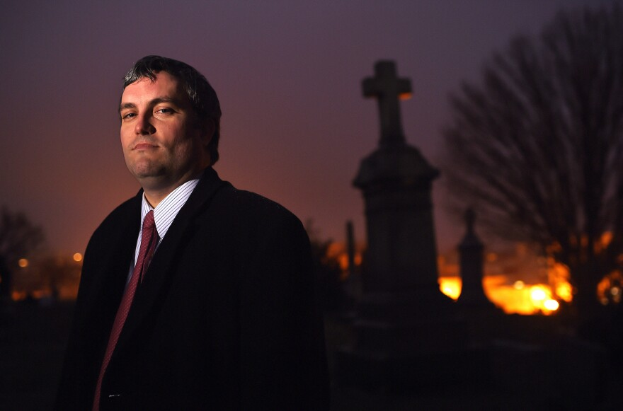 """Brett Talley stands in Holy Rood Cemetery in Washington, D.C., in 2014. Talley had been rated """"unanimously unqualified"""" for a lifetime judicial appointment and his nomination """"will not be moving forward,"""" according to a Trump administration official."""