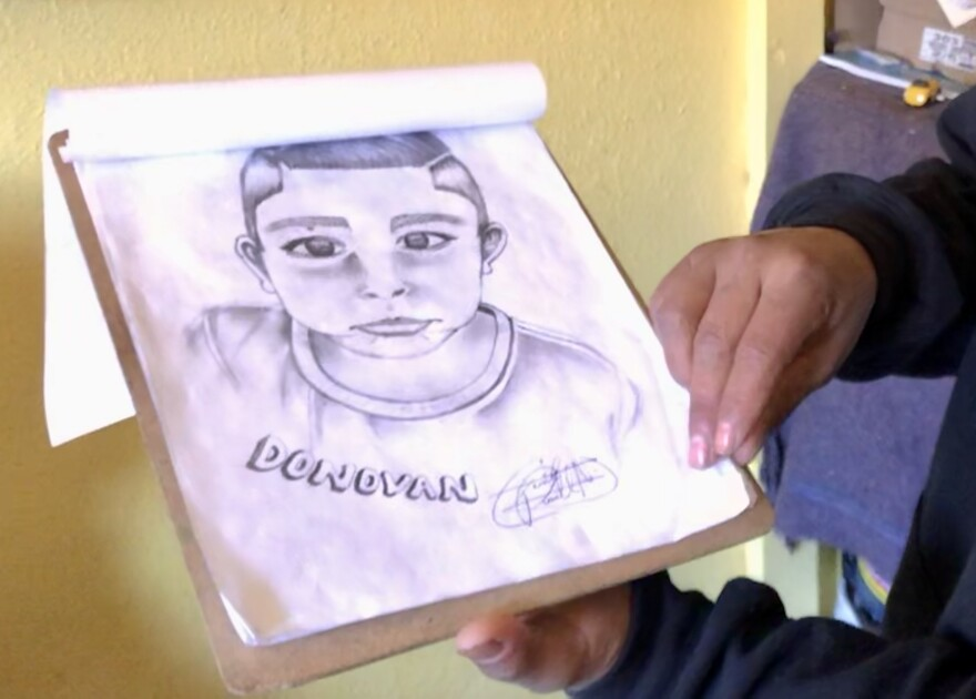 A man holds up a clipboard with a drawing of a young boy and the name Donovan written in bubble letters.