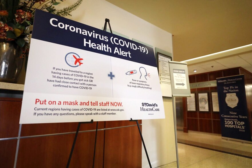 A sign tells visitors at St. David's Medical Center to alert staff if they've traveled to a region with cases of COVID-19 and have certain respiratory symptoms.