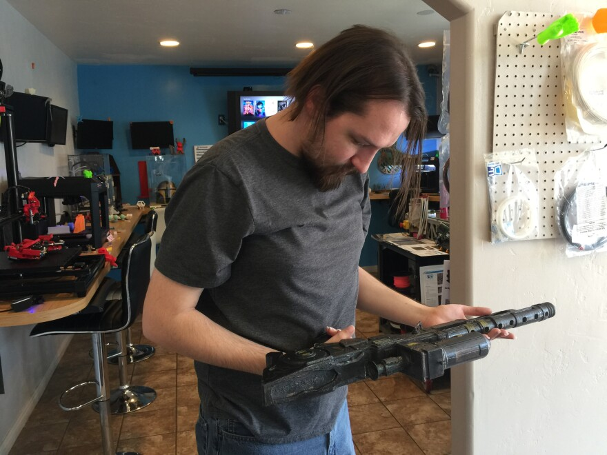 man holds a model of a black rifle made on a 3-D printer.