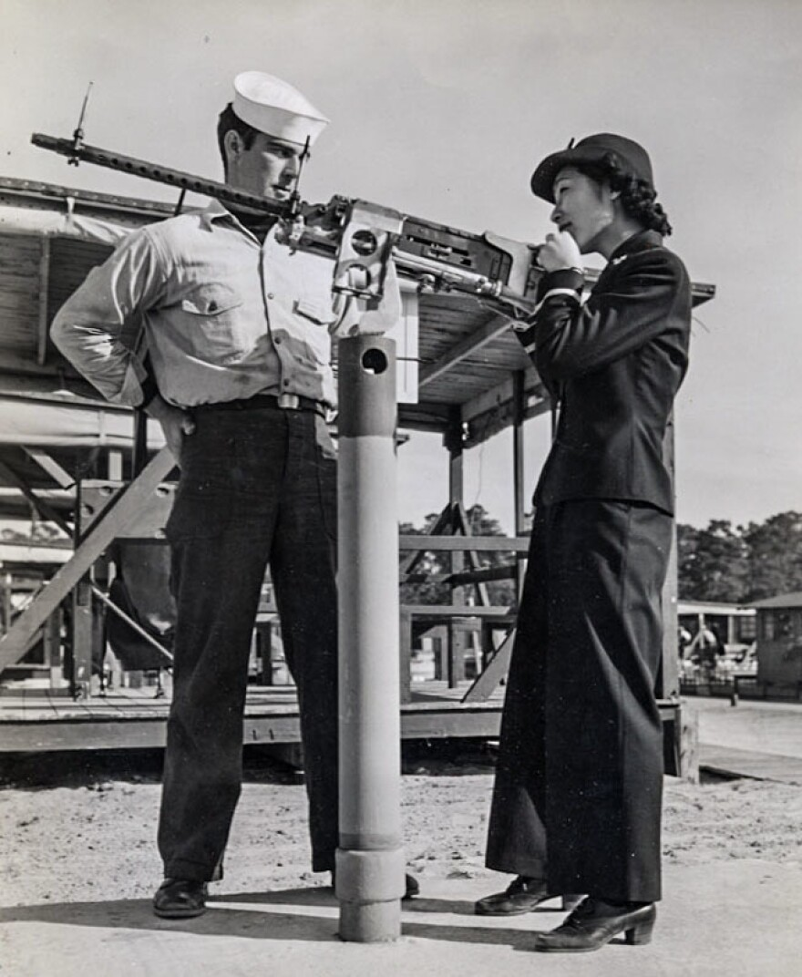 In 1943, Susan Ahn Cuddy is seen at the Pensacola U.S. Naval Air Station in Florida, instructing a sailor on how to fire a .50-caliber machine gun.