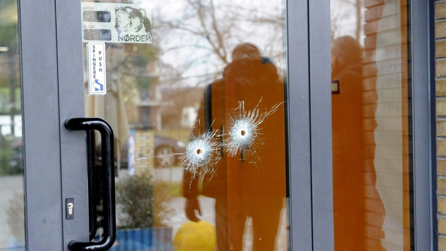 Bullet holes are seen in a glass door as police forensics officers carry out investigations in the area following the wounding of several foreign nationals in a drive-by shooting in Macerata.