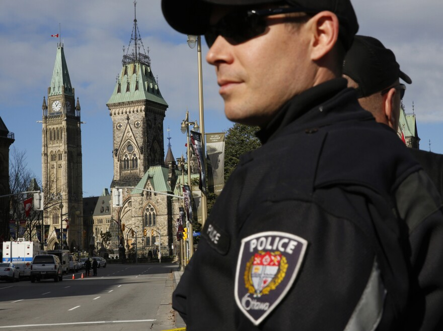 Ottawa police officers, with Parliament Hill in the background, guard the area around the National War Memorial in downtown Ottawa on Thursday.