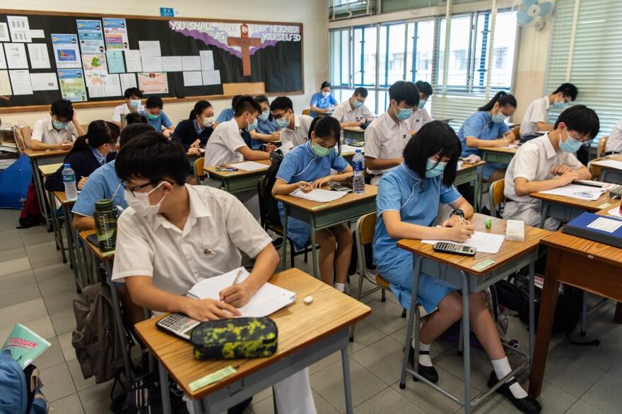 High school students wear masks inside a classroom.