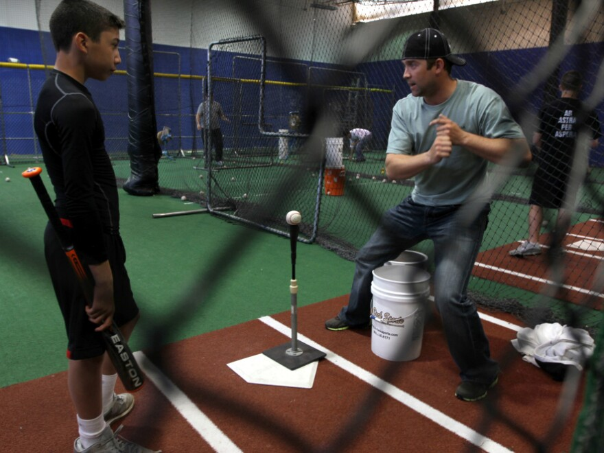 """Reid Gorecki coaches a young player in a batting cage. Remembering the first hit he got in the majors, Gorecki calls it """"a dream come true."""""""